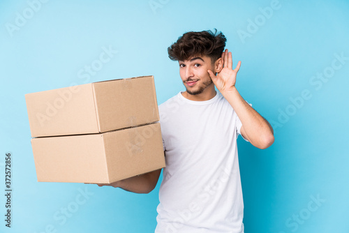 Papel de parede Young arab man holding boxes isolated trying to listening a gossip