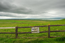 "Old Worn Warning Sign ""Private Property"" On A Fence By A Green Field, Grey Cloudy Sky, West Of Ireland. Nobody."