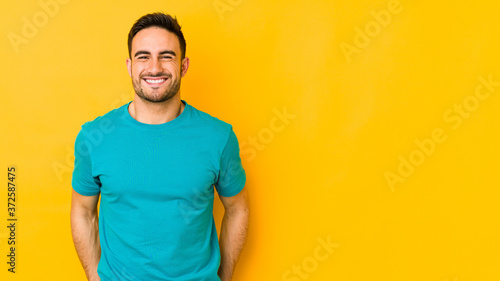 Young caucasian man isolated on yellow bakground laughs and closes eyes, feels relaxed and happy Wallpaper Mural