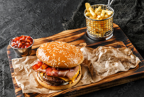 Fotografering Tasty burger with beef meat cutlet, slice of cheese, ham and spicy sauce on wooden board with french fries potatoes on black background