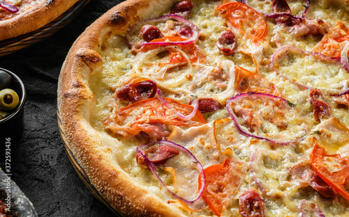 Pizza Pepperoni with prosciutto, sausage, cheese parmesan, tomatoes and onion rings on stone black background Fotobehang