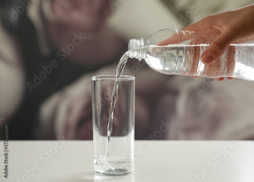 Fotografia, Obraz Woman pouring water from bottle into glass on table against blurred background,