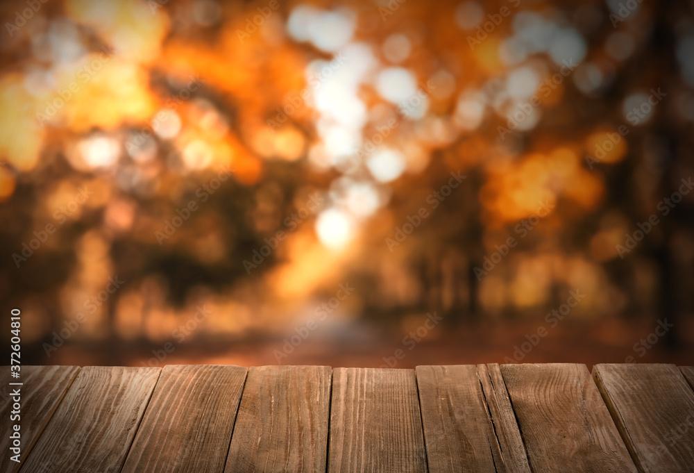 Fototapeta Empty wooden table in beautiful autumn park