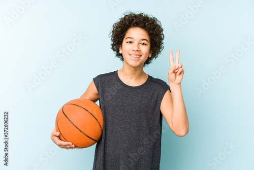 Fotografia Kid boy playing basketball isolated on blue background showing number two with fingers