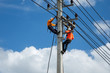 An electrician is on a light pole to maintain a high voltage line on a dangerous electric pole.