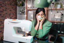 Craftswoman Using Modern Sewing Machine While Creating Masks With Green Pattern Near Lamp In Loft Style Workshop