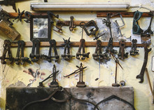 Set Of Various Metal Jewelry Instruments On Wooden Beam Representing Pliers And Bench Pins Near Saw Frames And Mirror On Concrete Weathered Wall In Studio