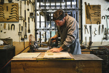 Concentrated Middle Aged Ethnic Artisan In Robe Working With Wooden Blocks At Table Using Drill While Stranding Near Window With Fence And Wall With Professional Tools