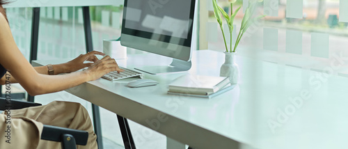 Fotografie, Obraz Female working on computer with copy space, supplies and flower vase decorated o