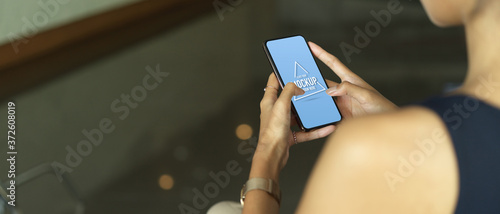 Fototapeta Female hands using mock up smartphone while relaxed sitting in cafe