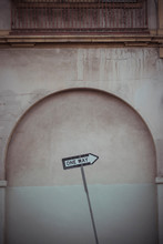 Arrow Shaped Inclined Signboard With Black Text One Way On White Background Directing To Right And Placed Against Shabby Stone Building Wall