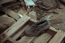 Dirty Boot Placed On Wood And Concrete Floor And Surrounded By Dusty Clothes In Shabby Facility Of Neglected Plant