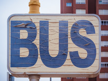 Shabby Weathered Rectangular Road Sign Indicating Bus Stop Point With Word Bus Written With Blue Letters On White Background And Placed Against Tall Modern Building In Daytime