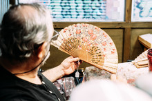 Painter Using Paintbrush To Draw On Hand Fan While Sitting At Messy Table And Working In Creative Workshop