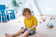 Little Upset Boy With Curly Hair Sitting On Parquet Floor Near Toys While Crying After Playing In Cozy Playroom With Tent