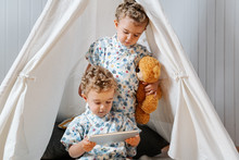 Adorable Little Twin Brothers In Similar Clothes Watching Video On Tablet While Sitting Under Tent With Toys In Cozy Nursery At Home