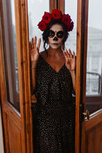 Full-length Photo Of Mexican Girl With Skull On Her Face. Lady In Black Polka Dot Outfit Opens Door To Balcony