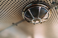Low Angle Of Small Round Metal Fire Alarm Lamp With Rusty Surface On Holey Ceiling In Fire Truck