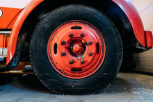 Big Black Rubber Wheel With Used Red Metal Rim And Many Fixing Nuts Under Shiny Car Fender Liner In Garage With Dirty Floor
