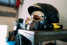 Modern Fireman Protective Plastic Hat With Yellow Lines On Shiny Surface On Ribbed Wooden Table In Room On Blurred Background