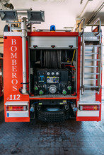 Red Fire Truck With Open Back Compartment With Hoses And Water Equipment Under Measuring Devices And Valves In Garage
