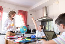 Adult Female Tutor Pointing With Finger At Globe Standing Near Concentrated Pupil In Headphones And Near Anonymous Boy With Laptop During Geography Lesson At Home During Geography Lesson In Kitchen