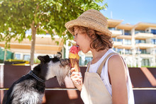 Side View Of Kid Licking Ice Cream Cone With Dog While Sitting On Bench During Summer Vacation