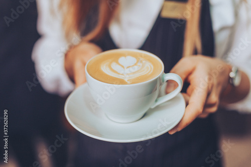 Fotografie, Obraz Barista offering a garnished latte espresso