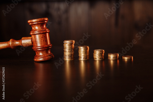 Photo TAX payment concept. Stack of coins with wooden judge gavel