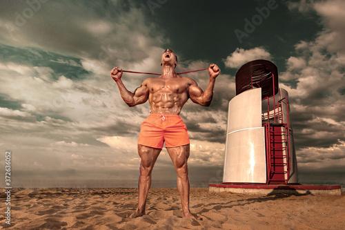 Fit athlete bodybuilder on the beach Tapéta, Fotótapéta