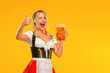 canvas print picture - Young sexy Oktoberfest girl waitress, wearing a traditional Bavarian or german dirndl. Woman serving big beer mugs with drink isolated on yellow background.