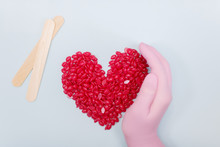 Red Color Depilation Wax Granules In The Shape Of A Heart On A Blue Background. Master's Hand In A Pink Glove. Epilation, Depilation, Removal Of Unwanted Hair With Wax. Selective Focus.