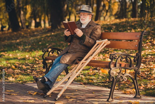 Photo Full length profile side photo of injured old man sit bench crutch enjoy fall fo