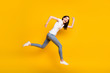 Full length body size view of her she pretty childish cheerful cheery thin girl sprinter jumping running having fun motion active life isolated bright vivid shine vibrant yellow color background