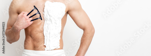 Obraz na płótnie Young caucasian man with beard holds razor shaves his chest with white shaving foam on white background