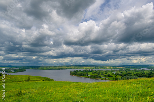 Fototapeta Summer landscape, a large full-flowing river, meadow flowers on the banks of the river, mighty clouds in the sky, a tourist walk along the Kama River obraz na płótnie