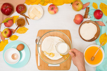 ingredients and recipe for homemade Apple cupcakes and muffins, top view light background, yellow leaves. the concept of fall baking and fall harvest. mixing flour, eggs and butter with women's hands