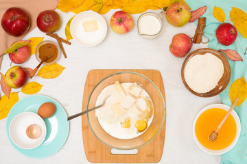 ingredients and recipe for homemade Apple cupcakes and muffins, top view light background, yellow leaves. the concept of fall baking and fall harvest. mixing flour, eggs and butter, knead the dough