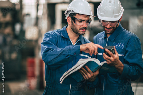 Tela Engineer service team looking at machine service manual text book, Working together as teamwork in factory