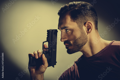 Foto Closeup photo of young brutal special agent holding gun