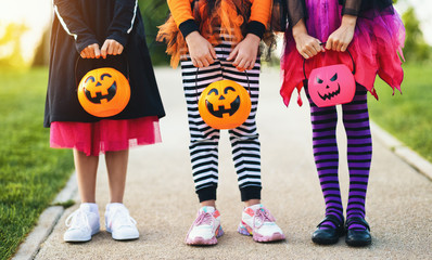 Happy Halloween! legs of funny children in carnival costumes outdoors