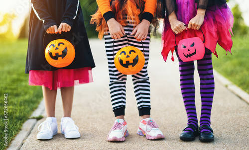 Foto Happy Halloween! legs of funny children in carnival costumes outdoors