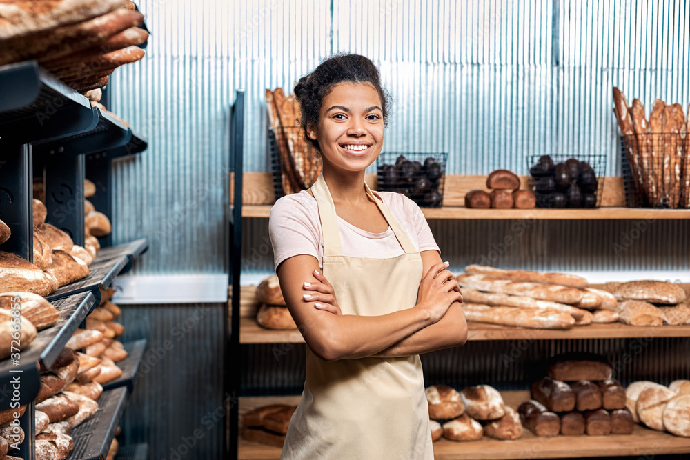 Fototapeta Young adult woman standing in family bakery