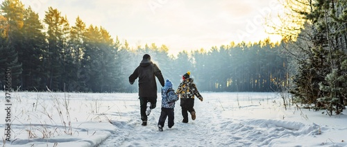 Vászonkép Father and two children in winter forest