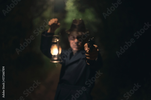 Foto Detective agent in a hat and coat is holding in hand a kerosene lamp and is aiming by a gun into a dark