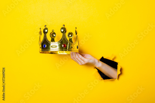 Female hand holds a gold crown on a bright yellow background. Canvas Print