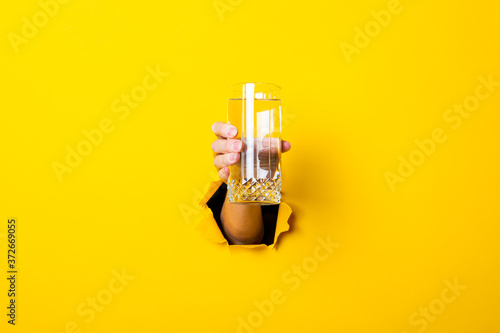 Fotografiet Female hand holding a glass of water on a bright yellow background