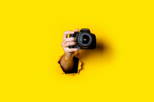 Man's Hand Holding A Camera On A Bright Yellow Background.