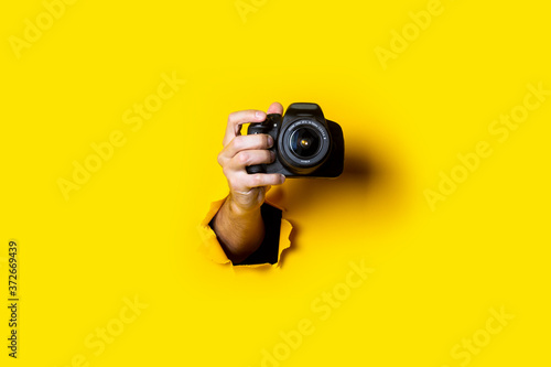 Leinwand Poster Man's hand holding a camera on a bright yellow background.