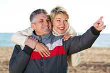 Glad Mature Couple Walks Outdoors And Point By Hand To Interesting Objects